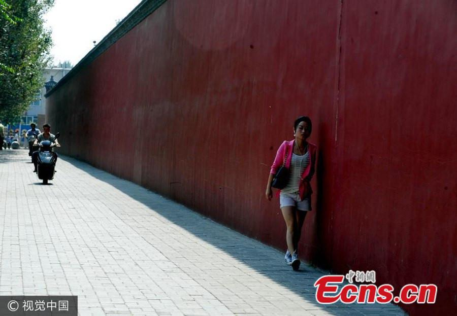 A woman clings to the wall to take advantage of a narrow strip of shade in Shenyang, Liaoning province, Sept 14, 2010. (Photo/VCG)