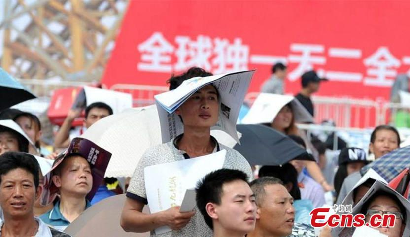 When filmstar Feng Shaofeng comes to Nanchang, Jiangxi province, he attracts a large audience May 10, 2015. As the temperature reaches 30 C, fans fold leaflets into hats in all kinds of shapes under the scorching sun. (Photo/China News Service)