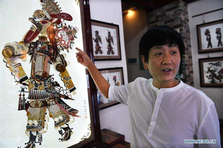 Shadow puppet artist Xue Hongquan introduces his creation in Weinan City, northwest China's Shaanxi Province, July 15, 2017. Xue, an inheritor of shadow puppet in Weinan City, combined the European ballet, American pop music with the Chinese traditional shadow puppet show. (Xinhua/Tao Ming)