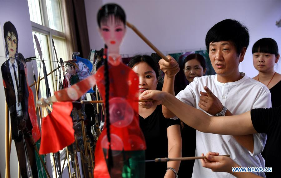 Shadow puppet artist Xue Hongquan and other performers discuss about improving the shadow puppet ballet in Weinan City, northwest China's Shaanxi Province, July 15, 2017. Xue, an inheritor of shadow puppet in Weinan City, combined the European ballet, American pop music with the Chinese traditional shadow puppet show. (Xinhua/Tao Ming)