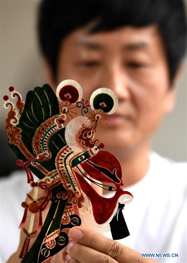 Shadow puppet artist Xue Hongquan works on a creation in Weinan City, northwest China's Shaanxi Province, July 15, 2017. Xue, an inheritor of shadow puppet in Weinan City, combined the European ballet, American pop music with the Chinese traditional shadow puppet show. (Xinhua/Tao Ming)
