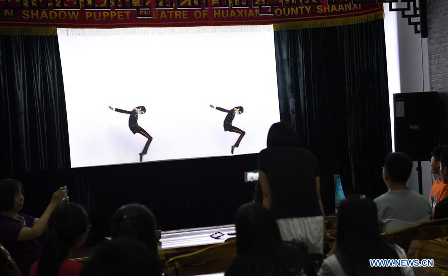 People watch shadow puppets showing Michael Jackson's dance in Xue Hongquan's theatre in Weinan City, northwest China's Shaanxi Province, July 15, 2017. Xue, an inheritor of shadow puppet in Weinan City, combined the European ballet, American pop music with the Chinese traditional shadow puppet show. (Xinhua/Tao Ming)