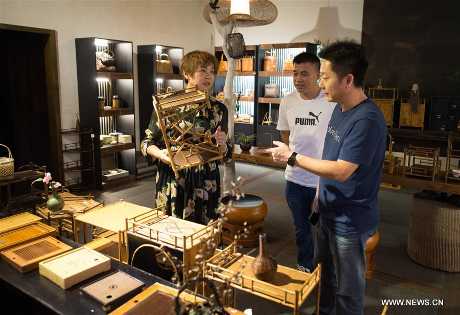 People choose bamboo goods at a display room in Anji County, east China's Zhejiang Province, Aug. 2, 2017. Anji County is a traditional producing area of bamboo industry. (Xinhua/Weng Xinyang)