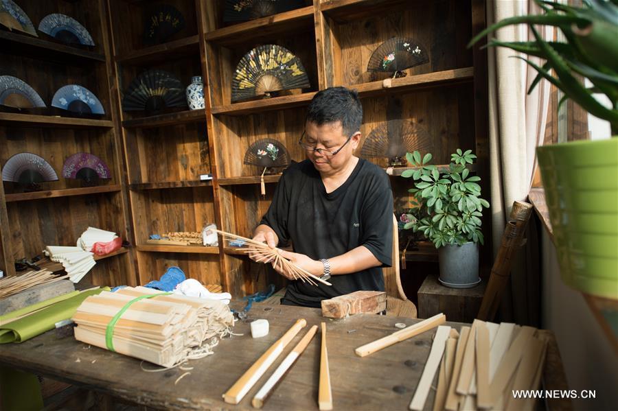 A fan maker makes folding fans at Zhangwu Town, Anji County, east China's Zhejiang Province, Aug. 2, 2017. Anji County is a traditional producing area of bamboo industry. (Xinhua/Weng Xinyang)