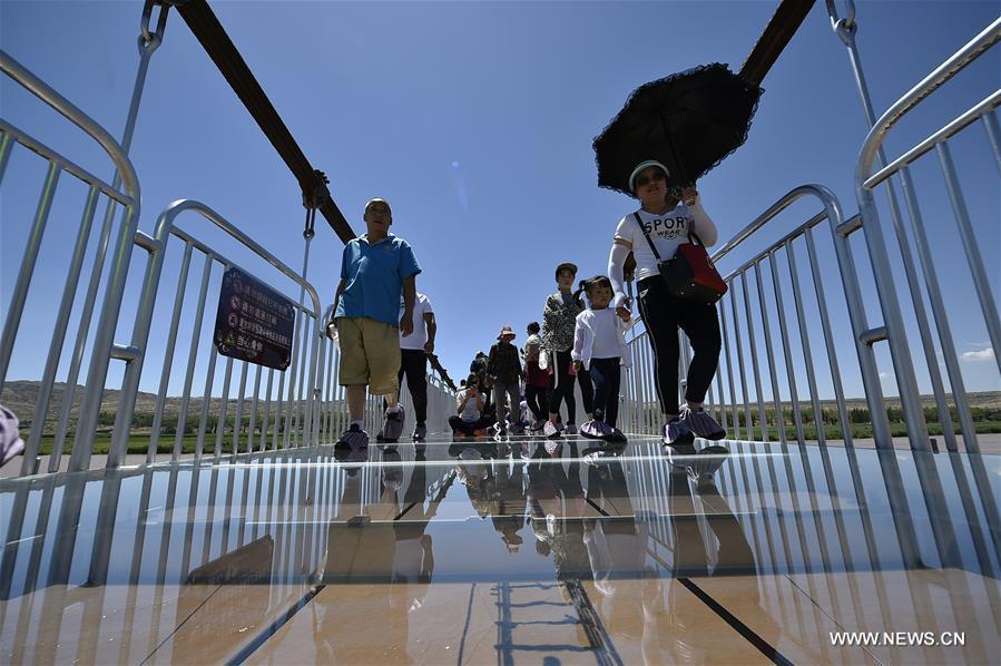 Tourists walk on a glass bridge across the Yellow River in Zhongwei, northwest China's Ningxia Hui Autonomous Region, Aug. 2, 2017. The 210-meter-long glass bridge was modified from an old suspension bridge by replacing the wooden deck with glass. (Xinhua/Li Ran)