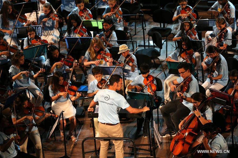 Ron Davis Alvarez, artistic leader of El Sistema Sweden, is conducting the Sistema Europe Youth Orchestra in the Odeon of Herodes Atticus in Athens, Greece, on Aug. 1, 2017. More than 421 El Sistema students of 27 nationalities from across Europe, aged from 10 to 20 years old, took part in the concert to celebrate the ability of music to unite nations, religions and cultures. (Xinhua/Marios Lolos)