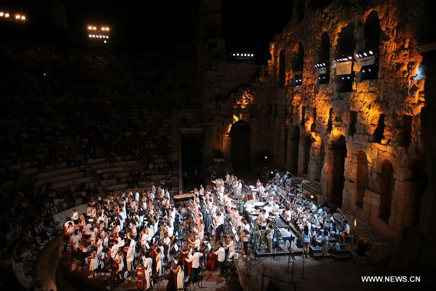 The advanced group of the Sistema Europe Youth Orchestra performs with a choir of children refugees living in Greece at the Odeon of Herodes Atticus in Athens, Greece, on Aug. 1, 2017. More than 421 El Sistema students of 27 nationalities from across Europe, aged from 10 to 20 years old, took part in the concert to celebrate the ability of music to unite nations, religions and cultures. (Xinhua/Marios Lolos)