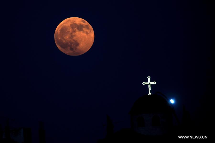 Photo taken on Aug. 7, 2017 shows the moon over a Catholic church after partial lunar eclipse over Amman, Jordan. (Xinhua/Mohammad Abu Ghosh)