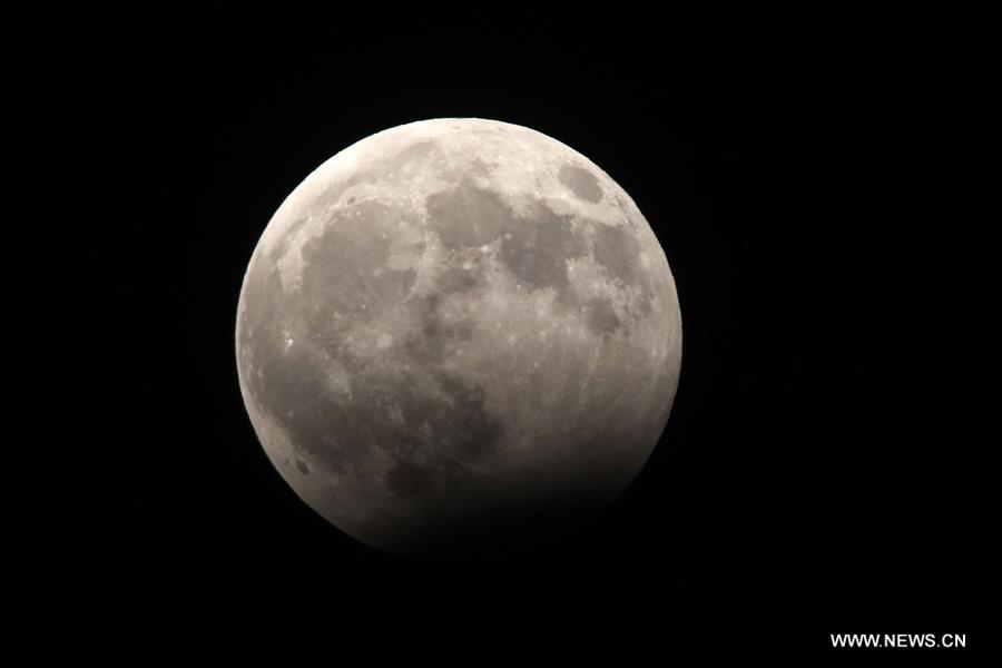 A portion of the moon crosses into the earth's shadow during partial lunar eclipse over Amman, Jordan, on Aug. 7, 2017. (Xinhua/Mohammad Abu Ghosh)