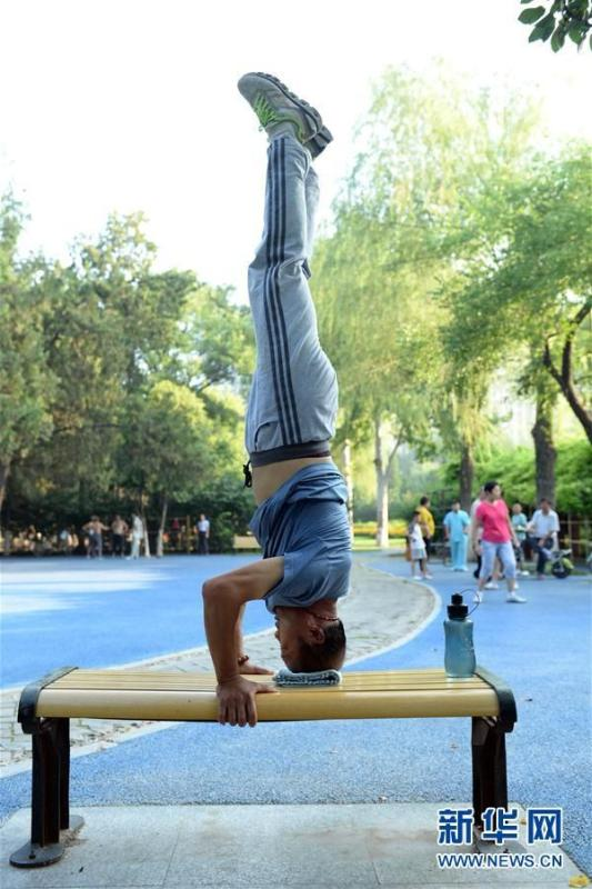 Wang Changli, 60, practices handstand in Liaocheng city, east China's Shandong province, on August 8, 2017. (Photo/Xinhua)