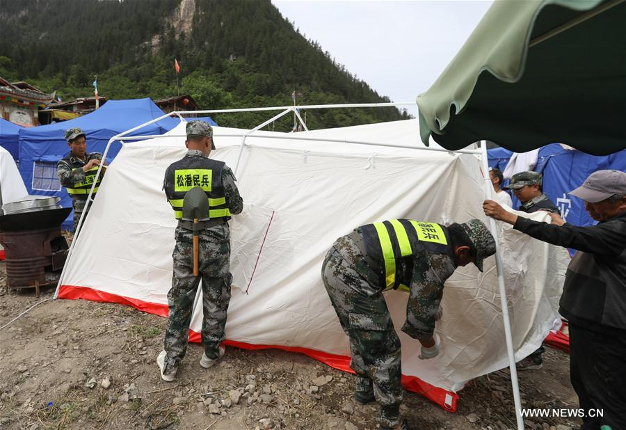Rescuers set up tents for local Tibetan villagers as temporary settlements in Shuzheng Tibetan Village of quake-hit Jiuzhaigou, southwest China's Sichuan Province, Aug. 10, 2017. Temporary settlements were established in Tibetan villages of Jiuzhaigou after a 7.0-magnitude earthquake struck Jiuzhaigou County on Tuesday. Relief supplies have been provided to aid quake-affected people. (Xinhua/Jiang Hongjing)