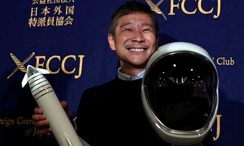 Yusaku Maezawa, SpaceX BFR's first private passenger, poses with a miniature rocket and space helmet prior to the start of a press conference at the Foreign Correspondents' Club of Japan in Tokyo on Tuesday. Photo: AFP