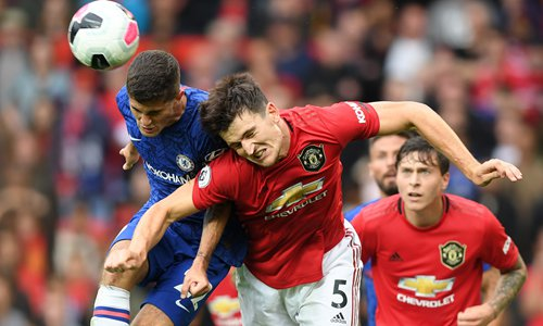 Christian Pulisic (left) of Chelsea battles for a header with Harry Maguire of Manchester United on Sunday in Manchester, England. Photo: VCG