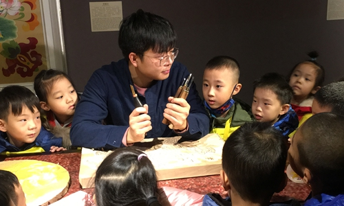 Xi Wang teaches local children Yangliuqing Woodblock Printing techniques, Jan. 10, 2020. (Photo provided to Xinhua)