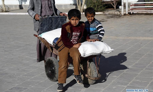 Yemeni children sit on a wheelbarrow loaded with food rations provided by the World Food Programme (WFP) at a food distributing center in Sanaa, Yemen, on Feb. 11, 2020. Yemen has been mired in a civil war since late 2014, when the Iran-backed Houthis seized control of much of the country's north and forced the Saudi-backed government of President Abd-Rabbu Mansour Hadi out of Sanaa. The war has killed tens of thousands of people, displaced 3 million and pushed the country to the brink of famine. (Photo by Mohammed Mohammed/Xinhua)