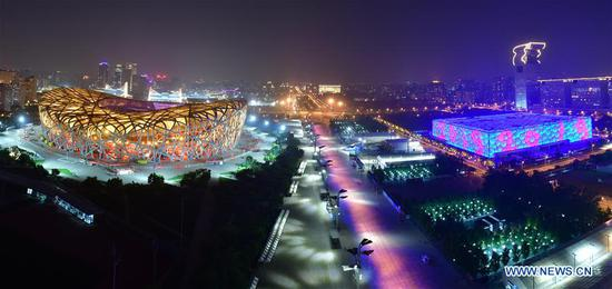 Photo taken on May 14, 2019 shows the night view of the National Stadium, also known as the Bird's Nest, and the National Swimming Center, also known as the Water Cube, in Beijing, capital of China. Roads and buildings were illuminated Tuesday evening before the upcoming Conference on Dialogue of Asian Civilizations (CDAC) in Beijing. (Xinhua/Li He)