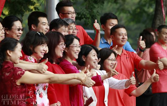 China's national college entrance examinations, known as gaokao, started Friday morning. A record over 10.31 million students, which roughly equals the population of Portugal, applied to take the exams this year. At the examination hall of the Beijing National Day School, parents and teachers cheer on the candidates. (Photos: Li Hao/GT)