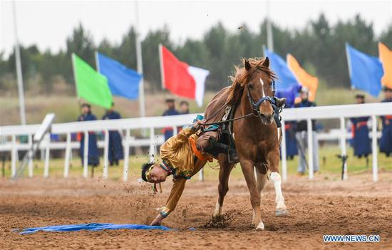 A man picks up a hada when riding a horse during the Genghis Khan Chagan Suluk Nadam Fair in Ejin Horo Banner of Ordos City, north China's Inner Mongolia Autonomous Region, April 24, 2019. The two-day fair kicked off on Wednesday, including a variety of traditional activities. (Xinhua/Peng Yuan)