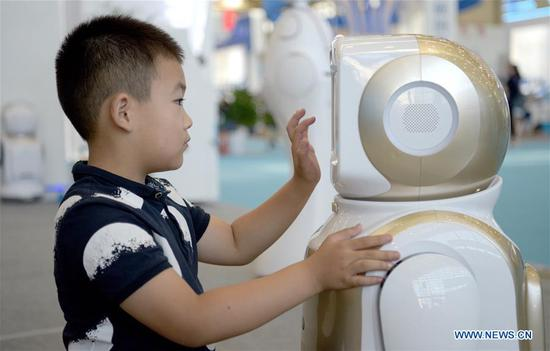 A child interacts with an android during the 14th China Xi'an International Science & Technology Industry Expo and Hard & Core Technology Industry Expo at Qujiang International Conference and Exhibition Center in Xi'an, capital city of northwest China's Shaanxi Province, Aug. 15, 2019. The expo opens on Thursday and will showcase fruits covering fields including artificial intelligence, aerospace, biological technology and information technology. (Xinhua/Liu Xiao)