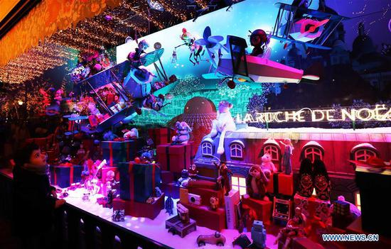 A boy enjoys the Christmas window at Galeries Lafayette department store in Paris, France, Nov. 24, 2019. The city of Paris is decorated with Christmas trees and decorations for the festival season. (Xinhua/Gao Jing)