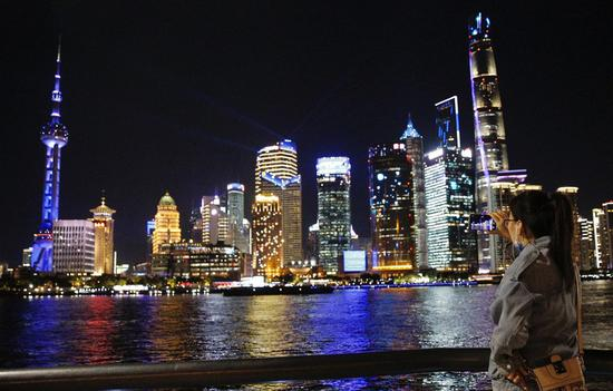 A tourist records a light show via mobile phone at the Bund in Shanghai, east China, Nov. 4, 2020. (Xinhua/Zhang Yuwei)