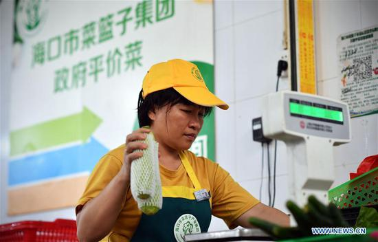 A seller weighs vegetables at a market in Haikou, capital of south China's Hainan Province, July 11, 2018. More vegetables are supplied by Haikou Shopping Basket Industry Group Company to stabilize the price of vegetables, as Haikou entered off-season vegetable production since May. (Xinhua/Guo Cheng)