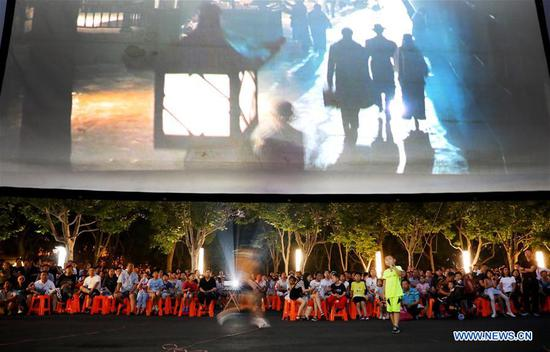 People watch a film shown in an evening open-air cinema at Minhang Sports Park in east China's Shanghai, July 7, 2019. Shanghai authorities have arranged more than 200 open-air film sessions as a summer entertainment for the public between July and September. (Xinhua/Fang Zhe)