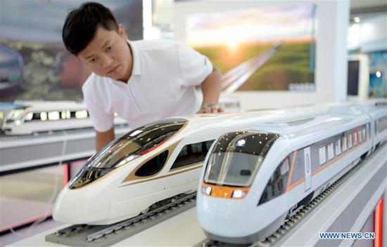A visitor views bullet train models during the 14th China Xi'an International Science & Technology Industry Expo and Hard & Core Technology Industry Expo at Qujiang International Conference and Exhibition Center in Xi'an, capital city of northwest China's Shaanxi Province, Aug. 15, 2019. The expo opens on Thursday and will showcase fruits covering fields including artificial intelligence, aerospace, biological technology and information technology. (Xinhua/Liu Xiao)