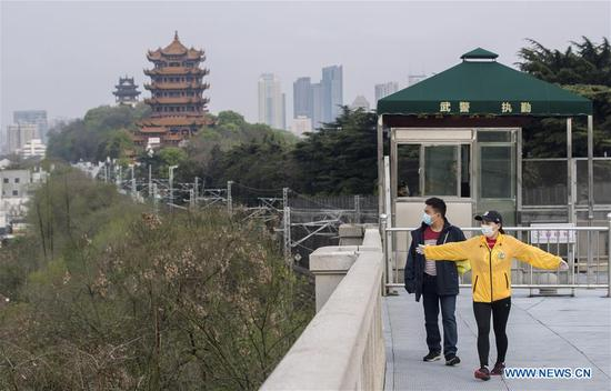 People walk on the Yangtze River Bridge in Wuhan, central China's Hubei Province, March 25, 2020. Daily life of people in Wuhan is gradually recovering as the epidemic outbreak has been subdued. (Xinhua/Fei Maohua)