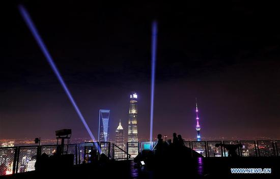 Workers adjust equipment for a light show at the Sinar Mas Plaza in Shanghai, east China, Oct. 26, 2020. A light show will be held on Nov. 5 to celebrate the opening of the third China International Import Expo (CIIE), which will take place in Shanghai from Nov. 5 to 10. (Xinhua/Fang Zhe)