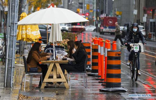 Customers dine at the outdoor area of a restaurant during a rainy day in Toronto, Canada, on Oct. 27, 2020. Canada hit another grim milestone on Tuesday as the country's death toll of COVID-19 reached 10,001, according to CTV. (Photo by Zou Zheng/Xinhua)