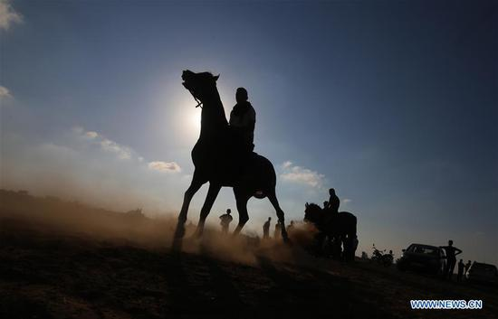 Palestinian men are silhouetted against sunshine as they ride their horses in a local horse race in the southern Gaza Strip city of Rafah, on Sept. 9, 2018. (Xinhua/Khaled Omar)