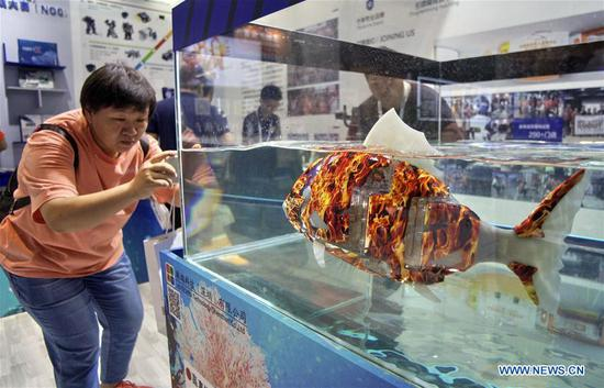 A visitor takes photos of a bionic robot fish during the 2019 World Robot Conference in Daxing District of Beijing, capital of China, Aug. 20, 2019. The 2019 World Robot Conference, themed