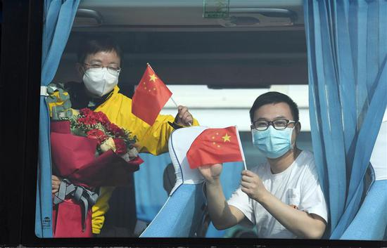 Medics supporting virus-hit Hubei Province wave on the bus to greeters upon their arrival at Guiyang Longdongbao International Airport in Guiyang, southwest China's Guizhou Province, March 20, 2020. Medical assistance teams from Guizhou, which consists of 433 members, left Hubei Province as the epidemic outbreak in the hard-hit province has been subdued. (Xinhua/Yang Wenbin)