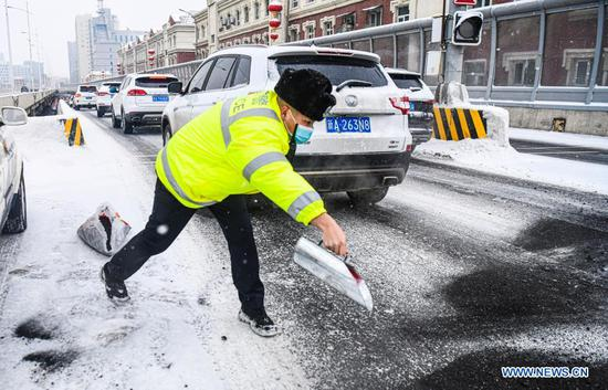 A police officer pours cinders on a street to make it less slippery amid snowfall in Urumqi, capital of northwest China's Xinjiang Uygur Autonomous Region, Nov. 19, 2019. Days of continuous snowfall has left streets wet and slippery in the city of Urumqi. (Xinhua/Wang Fei)