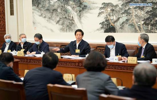 Li Zhanshu, chairman of the National People's Congress (NPC) Standing Committee, takes part in the group discussion to review the work report of the NPC Standing Committee, which will be submitted to the annual assembly of the legislature in March for deliberation, during the 26th session of the 13th NPC Standing Committee at the Great Hall of the People in Beijing, capital of China, Feb. 27, 2021. (Xinhua/Li Tao)
