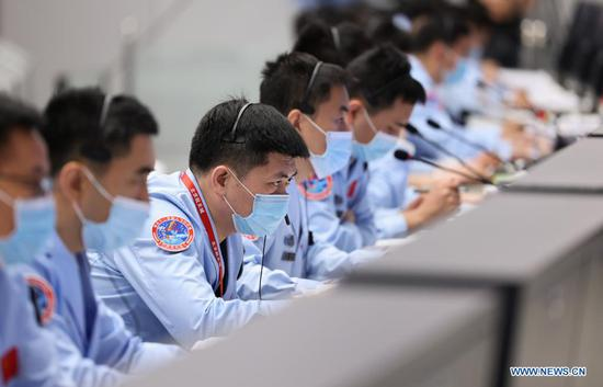 Technical personnel work at Beijing Aerospace Control Center in Beijing, capital of China, on July 4, 2021. Chinese astronauts Liu Boming and Tang Hongbo had both slipped out of the space station core module Tianhe by 11:02 a.m. (Beijing Time) on Sunday, starting extravehicular activities (EVAs), according to the China Manned Space Agency (CMSA). Donning new-generation homemade EMU (extravehicular mobility unit) spacesuits Feitian, meaning flying to space, the two astronauts have completed installing the foot restraints and extravehicular working platform on the mechanical arm, the CMSA said. They will continue to work together to install other relevant extravehicular equipment with the aid of the mechanical arm, it said. Astronaut Nie Haisheng has been staying inside Tianhe in cooperation with Liu and Tang for their EVAs. (Xinhua/Jin Liwang)
