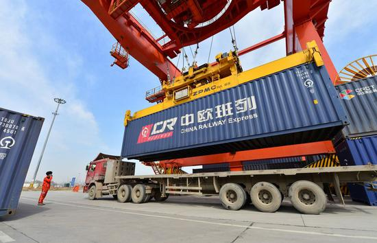 A worker directs container hoisting operation of a China-Europe freight train at a logistic station in Xinzhu Railway Station in Xi'an, northwest China's Shaanxi Province, March 11, 2020. (Photo by Tang Zhenjiang/Xinhua)