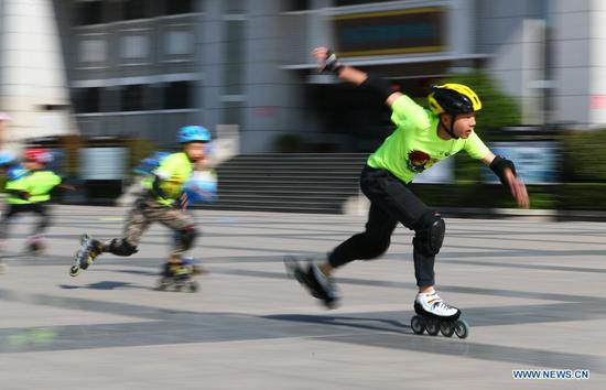 Children roller-skate on a square in Zaozhuang, east China's Shandong Province, May 2, 2021. Sunday marks the second day of China's five-day May Day holiday. (Photo by Li Zhijun/Xinhua)