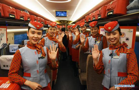 Train conductors wave on a tourism experience train in east China's Shandong Province, Nov. 24, 2019. A tourism experience train of high-speed rail line circling eight cities of Shandong Province started its journey from Jinan West Railway Station to the other cities, including Linyi, Rizhao and Qingdao, on Sunday, with specialties of the eight cities on display on the train. (Xinhua/Wang Kai)