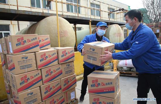 Workers transport disinfectants at a workshop in Yuncheng City, north China's Shanxi Province, Jan. 27, 2020. To help fight the outbreak of pneumonia caused by novel coronavirus, workers in factories in Shanxi work overtime to meet with the increasing need. (Photo by Bao Dongsheng/Xinhua)