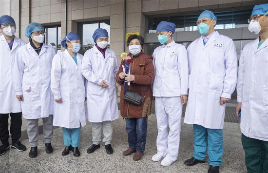Ms Xie, the 600th cured patient of COVID-19 at the east branch of Renmin Hospital of Wuhan University, poses for a photo with renowned Chinese epidemiologist Li Lanjuan and other doctors at the hospital in Wuhan, central China's Hubei Province, March 16, 2020. The 600th patient confirmed of novel coronavirus infection has been discharged from the east branch of the hospital on Monday. (Xinhua/Cai Yang)