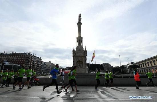 Runners pass by the Columbus Square during the Madrid Race in March Against Cancer in Madrid, Spain, April 15, 2018. The race was held by the Spanish Association Against Cancer, with the purpose of raising public attention on anticancer and having healthy lifestyle. (Xinhua/Guo Qiuda)