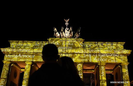 Silhouettes of visitors are seen against the illuminated Brandenburger Gate during the 2018 Festival of Lights in Berlin, capital of Germany, on Oct. 5, 2018. Berlin turned into a city of light art with the opening of its Festival of Lights on Friday which will last from Oct. 5 to Oct. 14. (Xinhua/Shan Yuqi)