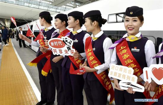 Attendants of the G2 bullet train hold sign boards to promote the first China International Import Expo (CIIE) at Hongqiao Railway Station in east China's Shanghai, Oct. 10, 2018. Railway authorities have launched a campaign on Wednesday to promote the upcoming first CIIE on bullet trains running on the Beijing-Shanghai high-speed railway. (Xinhua/Chen Fei)