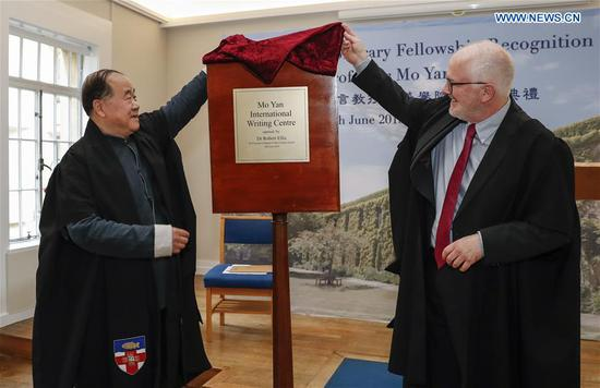 Chinese writer and Nobel laureate Mo Yan (L) and Regent's Park College principal Robert Ellis unveil the Mo Yan International Writing Center during the Honorary Fellowship Recognition Ceremony at University of Oxford, Britain, on June 12, 2019. Mo Yan was awarded Wednesday the Honorary Fellowship by Regent's Park College, University of Oxford, in recognition of his contribution to Chinese and world literature. The college principal Robert Ellis presented the gown and stole to Mo at the ceremony. They unveiled together a new international writing center named after Mo. (Xinhua/Han Yan)