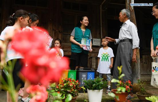A vounlteer (C) shares knowledge of garbage sorting with locals at Jianling Village in Dayan Township of Ningbo City, east China's Zhejiang Province, June 30, 2019. Jianling has been chosen to be a pilot village in Nov. 2018 for practising garbage processing in Dayan Township. (Xinhua/Huang Zongzhi)