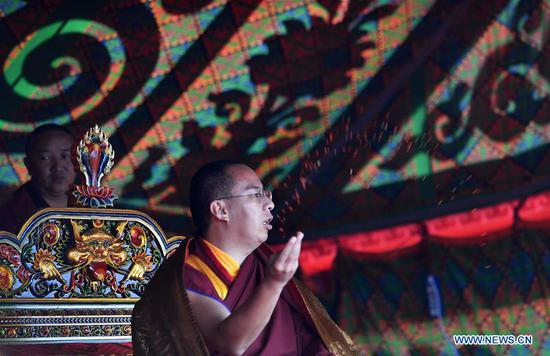 The 11th Panchen Lama Bainqen Erdini Qoigyijabu, also vice president of the Buddhist Association of China, worships on the bank of Nam Co Lake in southwest China's Tibet Autonomous Region, Aug. 7, 2019. (Xinhua/Chogo)