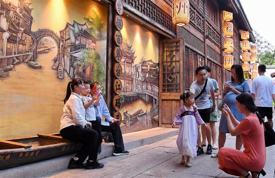 Tourists pose for photos at Shangxiahang traditional block in Fuzhou, southeast China's Fujian Province, Sept. 15, 2019. Fujian Province received over 5 million visitors during the three-day Mid-Autumn Festival holiday. (Xinhua/Lin Shanchuan)