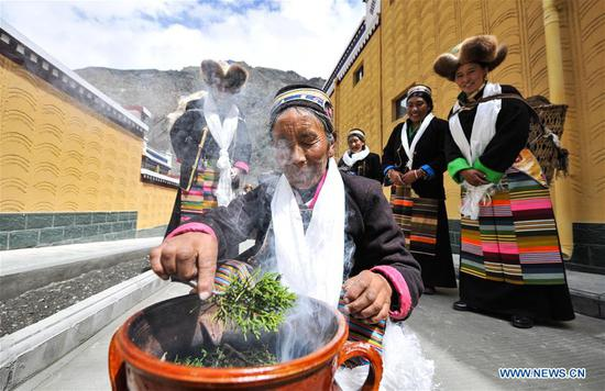 Villager Dainzin Quzhen (front) holds a traditional rite in front of her new house in Lhozhag Town of Lhozhag County, Shannan City, southwest China's Tibet Autonomous Region, Sept. 21, 2019. A total of 88 villagers from 28 households moved to their new two-story dwellings to improve housing conditions. (Xinhua/Jigme Dorje)